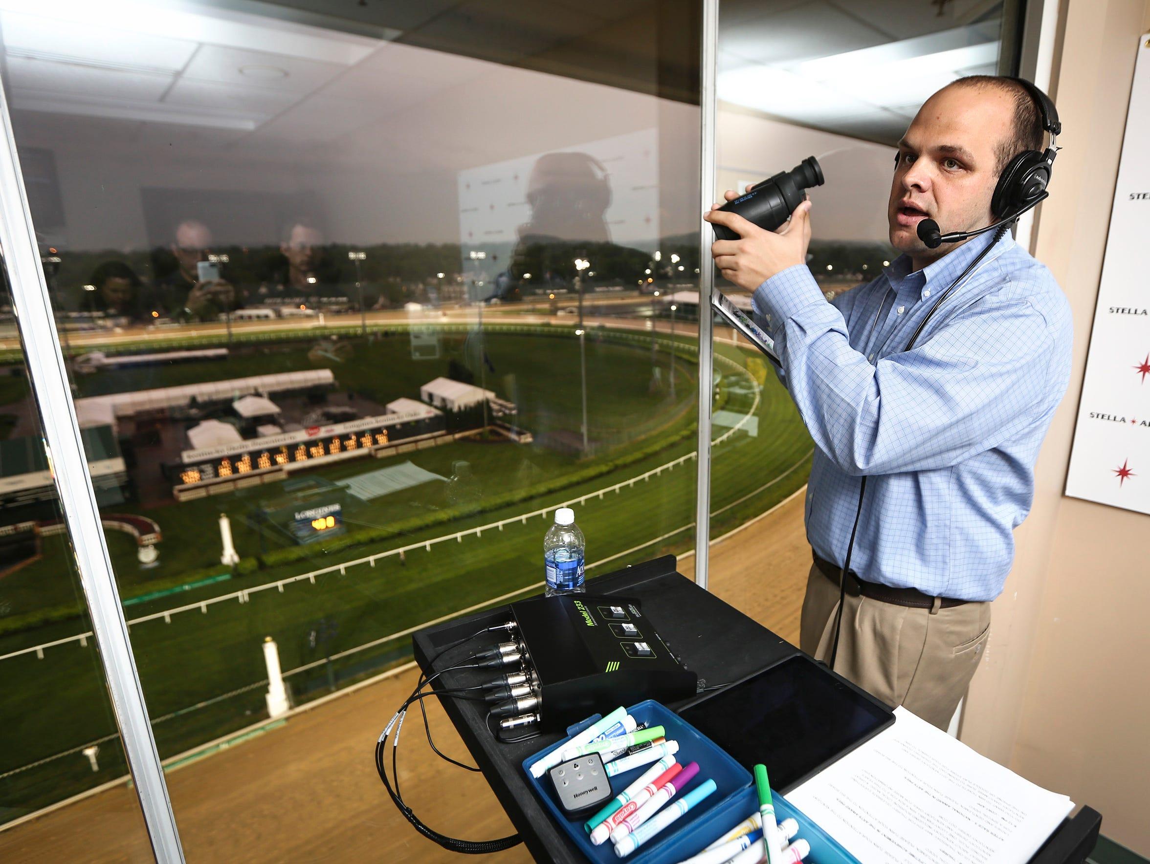 Churchill Downs announcer Travis Stone uses his binoculars