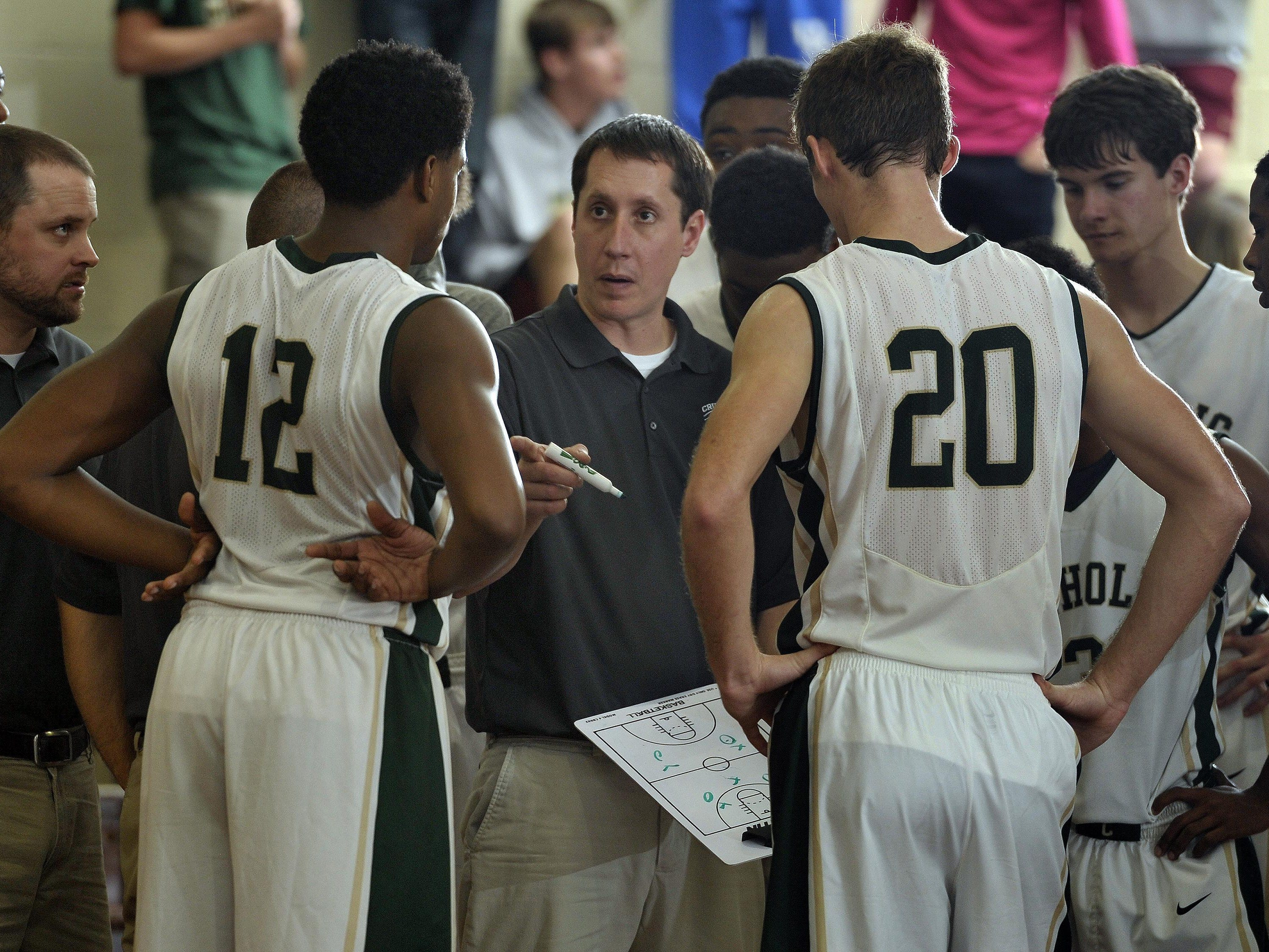 Catholic coach Nick Mead tries to map out a strategy for his team in the closing minutes of their game in 2014 against Lakeshore High.
