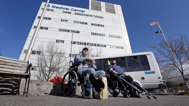 In this Monday, March 30, 2015 photo, Army veteran Michael Thrun, left, and Navy veteran Thomas Berry sit in wheelchairs as they wait for their rides following treatment at the Veterans Administration Puget Sound Medical Center in Seattle.