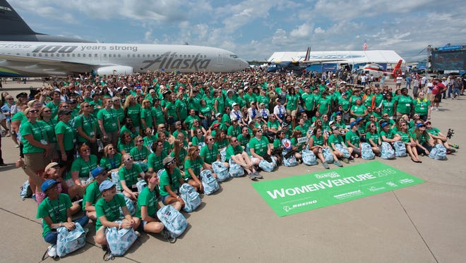 The assembled group participating in EAA's WomenVenture poses for a photo in front of an Alaska Airlines passenger jet. The Boeing jet was flown into Wittman Regional Airport by an all-female crew for the event on July 27, 2016, in Oshkosh.