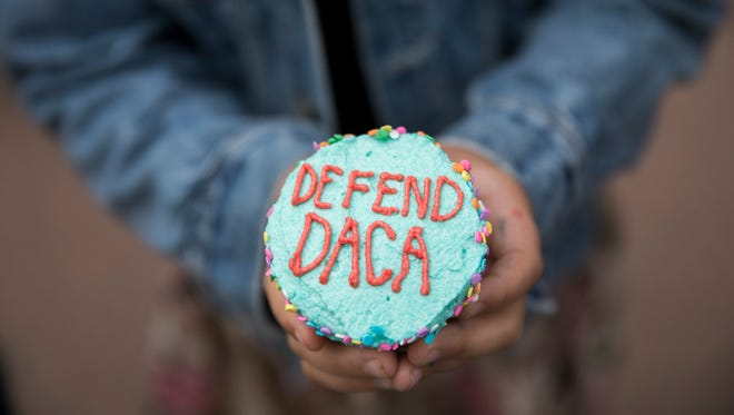 A girl hands out cupcakes at a protest against the announcement that the Trump administration is ending the Deferred Action for Childhood Arrivals program, known as DACA, in Minneapolis, Tuesday, Sept. 5, 2017.