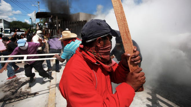 Teachers clash with riot police as tear gas spreads in front of the Guerrero state congress building in the city of Chilpancingo, Mexico.