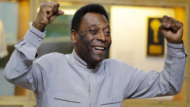 Soccer great Pele poses for photos during the inauguration of the Pele Museum, in Santos, Brazil.