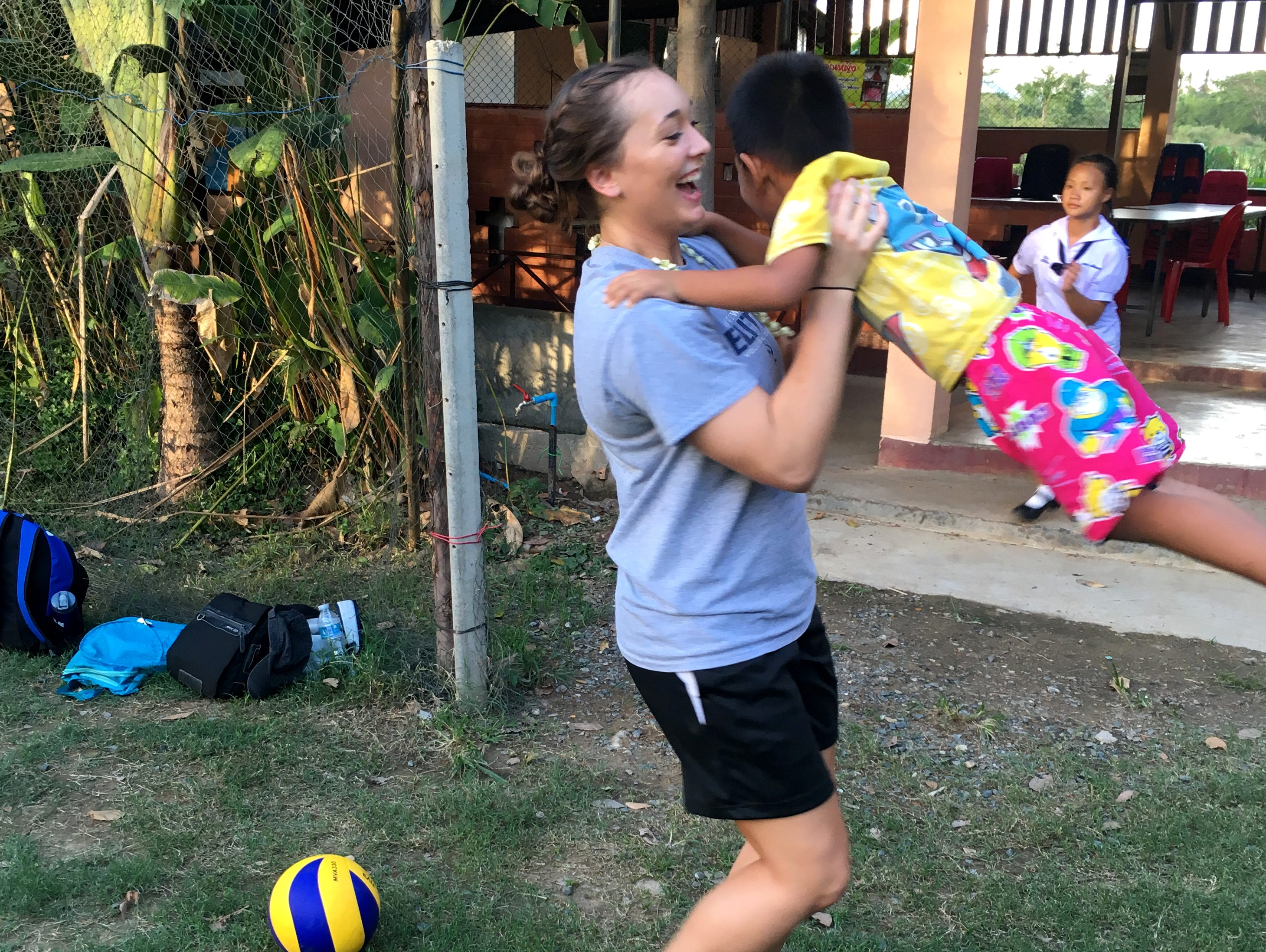 Willard's Makenzie Bouse (center) plays with a Thai child at an orphanage during Bouse's visit to Thailand on an Athletes in Action volleyball mission trip.