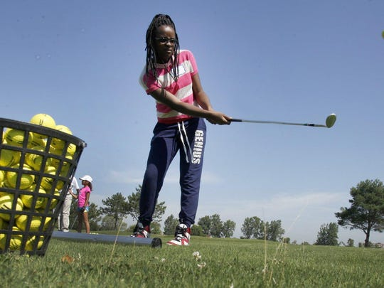Nia Rogan, 12, of Eastpoint practices her chipping at the LPGA-USGA golf program at the Belle Isle Golf Center in Detroit on Monday.