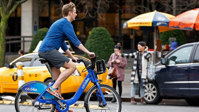 Wearing shorts, sneakers and no socks, a man rides a rental bike through a downtown Manhattan street on Christmas Eve, Thursday, Dec. 24, 2015, in New York, as warm temperatures, rising into the 70's in New York, shattered previous records.