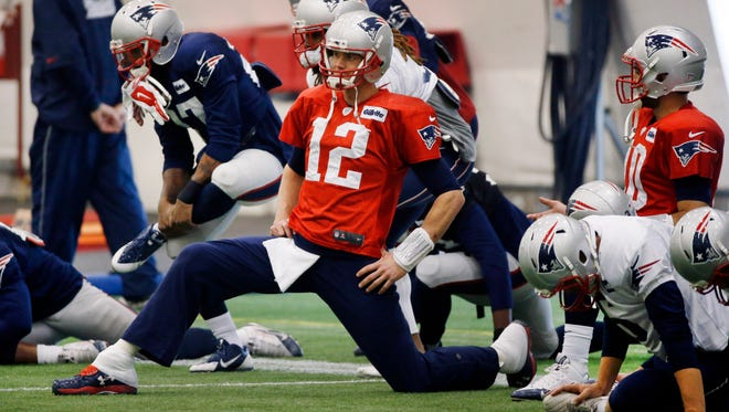 New England Patriots quarterback Tom Brady (12) stretches with his teammates as they warm up for team football practice in Foxborough, Mass., Thursday, Jan. 22, 2015. (AP Photo/Elise Amendola)