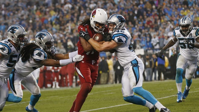 Arizona Cardinals WR Larry Fitzgerald runs towards the goal line wile tackled by Carolina Panthers safeties Tre Boston (33 left) and Colin Jones (42) in the first quarter during NFC Wild Card Playoff action at Bank of America Stadium in Charlotte, NC January 3, 2015.