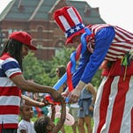 Kayden Batchelor, 2, reaches for a balloon hat made by Chad Estill, a stilt walking balloon artist for the Cincinnati Circus, during Independence Day festivities in Washington Park Saturday, July 4, 2015