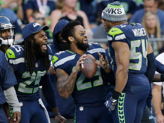 FILE - In this Aug. 25, 2017, file photo, Seattle Seahawks cornerback Richard Sherman, free safety Earl Thomas, center, and middle linebacker Bobby Wagner (54) react on the sideline during the second half of an NFL football preseason game against the Kansas City Chiefs, in Seattle. Thomas appears to be fully recovered from the injury that sidelined the safety late last season. The free safety is such a key cog in Seattle because of an ability to cover so much ground in the defensive backfield. (AP Photo/John Froschauer, File)