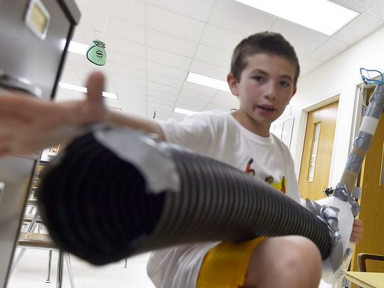 """Lucas Conard, 10, explains how his fish trap will work during the """"Inventors Showcase'' on the last day of Camp Invention at Southern Door Schools. The fish swims into the pipe after it smells bait in the top tube. It is trapped into the center milk carton after a lever is released."""