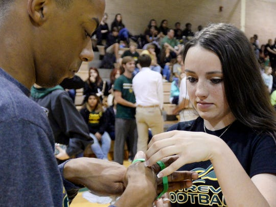 Daughter of Richard Lary, Ally Lary, gives Justin Brown the green rubber bracelet her dad wore all the time Monday morning memorial for Richard Lary.