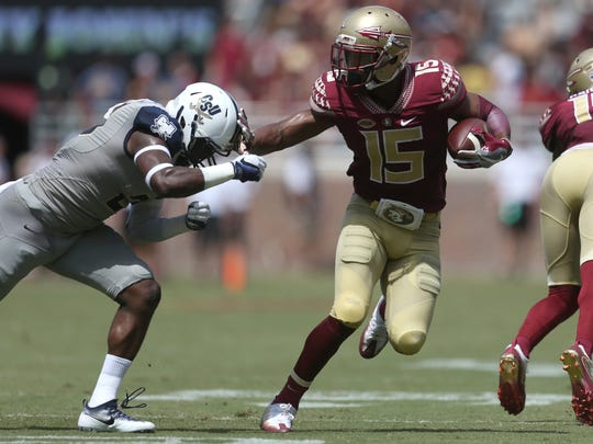 FSU's Travis Rudolph stiff arms Charleston Southern's Larenzo Mathis during their game at Doak Campbell Stadium Saturday.