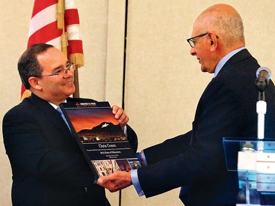 Chris Coxon, left, chief program officer for Educate Texas is presented with a book about El Paso by Richard Dayoub, president and CEO of the Greater El Paso Chamber of Commerce following Coxon's keynote address on the State of Education Thursday at the Marriott Hotel.