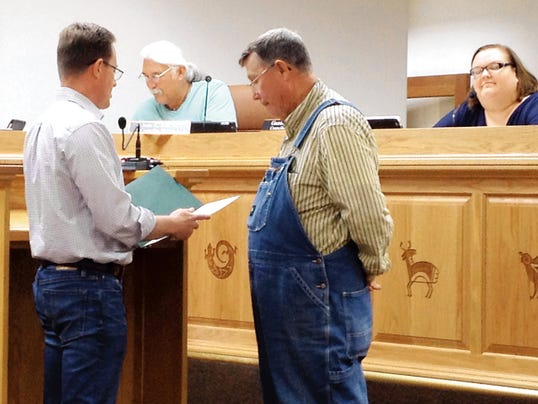 "Silver City Mayor Michael Morones, left, reads a proclamation declaring Sept. 26 a ""Day of Service"" to resident Gary Stailey while councilors Jose Ray and Guadalupe Cano look on during Tuesday's Town Council meeting. Randal Seyler Sun-News"
