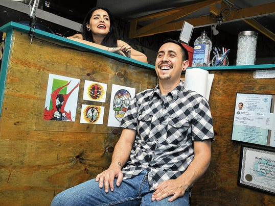 Jett Loe - Sun-News Las Cruces natives Anahy Nuñez and Aaron Valenzuela laugh in their tattoo parlor, Atom Bomb Studio, before a client arrives.