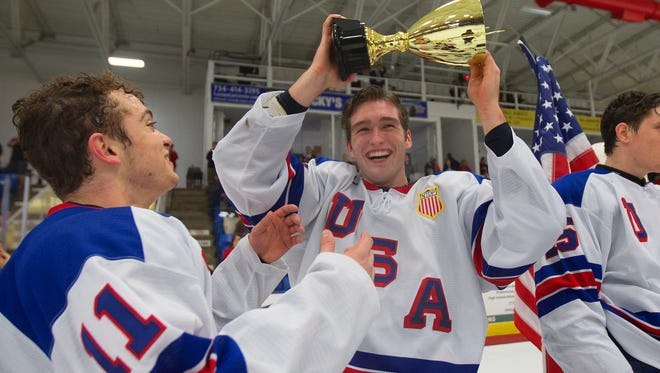 Scott Reedy hoists the Five Nations trophy after Team USA won the tourney title Saturday. At left is Jacob Tortora.