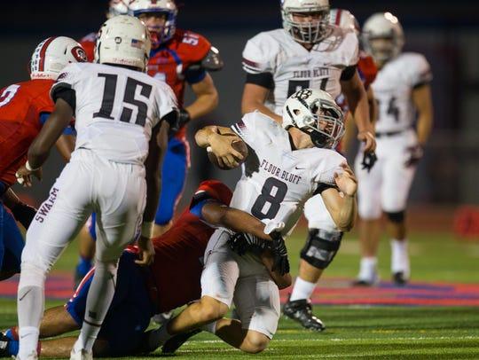 Flour Bluff's quarterback Branden Sherron is brought