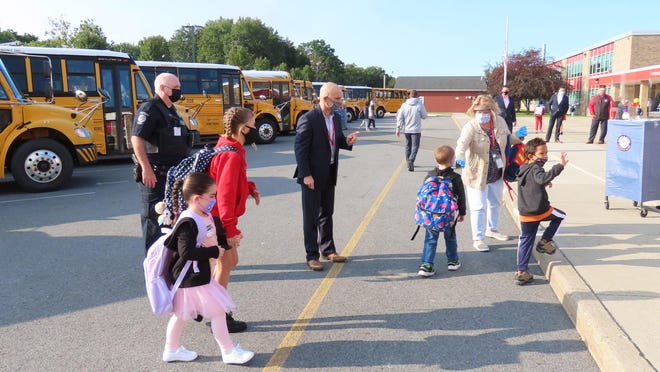 Anna S. Kuhl Elementary School Principal Brett Cancredi, center, joins teachers in welcoming students back to school on Monday.