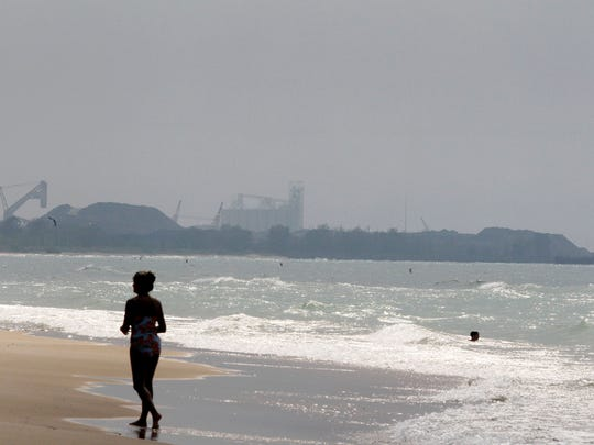 In this Star file photo, a woman walks along the beach on the Indiana shore of Lake Michigan, east of the Burns Harbor facility of ArcelorMittal steel mill.