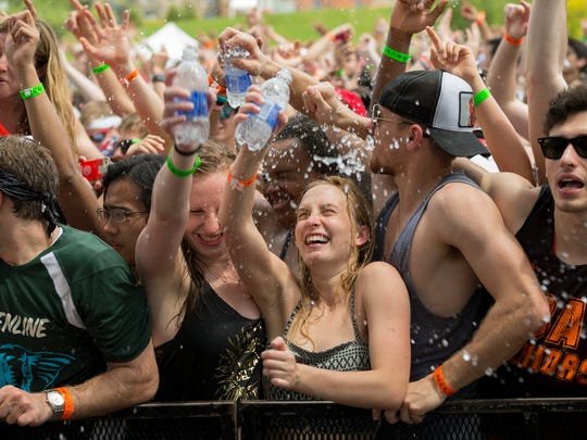 Cornell University students keep cool Thursday afternoon  as they listen to Walk the Moon at the Slope Day concert. Slope Day is the final day of classes at Cornell University.