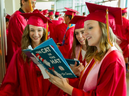 "From left, Ithaca High School graduates, Faith Crispell, of Slaterville, and Maddie Crooker of Ithaca, listen to Abby Cooper of Ellis Hollow, read Dr Suess's ""The Cat in the Hat,"" Thursday evening before graduation ceremonies at the Athletics and Events Center at Ithaca College."