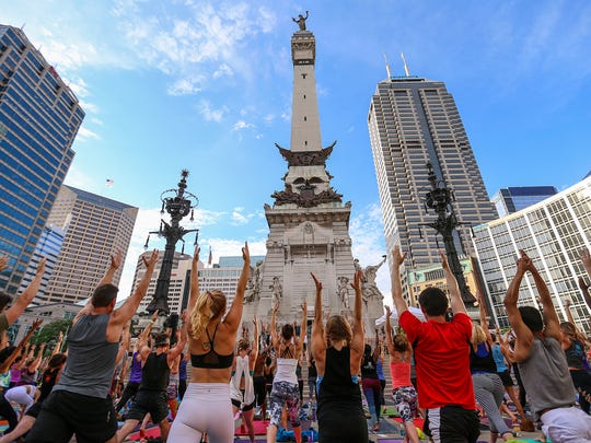 Hundreds of yogis practice yoga in front of the Soldiers' and Sailors' Monument for Monumental Yoga, celebrating the Summer Solstice and National Yoga Day on Monument Circle, downtown Indianapolis, Wednesday, June 21, 2017.