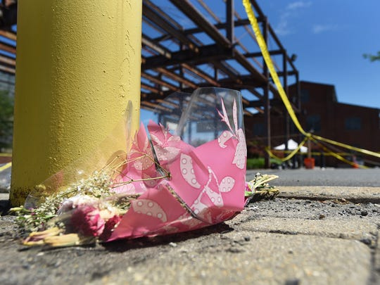 A bouquet of flowers left across the street from the crime scene at the Art All Night festival in Trenton on June 17.