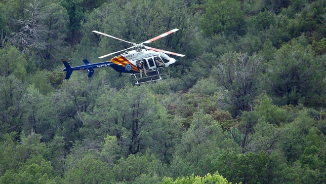 The Arizona Department of Public Safety searches for victims following a a flash flood near the Water Wheel campground in the Tonto National Forest Sunday, July 16, 2017 in Payson, Ariz.