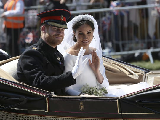 Britain's Prince Harry and Meghan Markle ride in an open-topped carriage after their wedding ceremony at St. George's Chapel in Windsor Castle in Windsor, near London, England, on May 19, 2018.