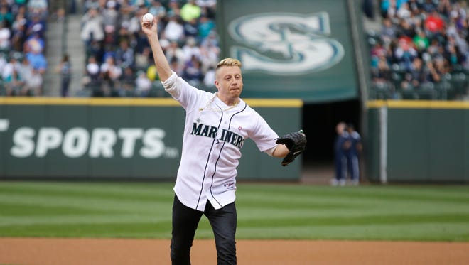 Rapper Macklemore throws out the first pitch of a baseball game between the Seattle Mariners and the New York Yankees, in Seattle on June 12, 2014.