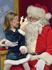 Four-year-old Isabella Jaczynski shows Santa her reindeer craft.
