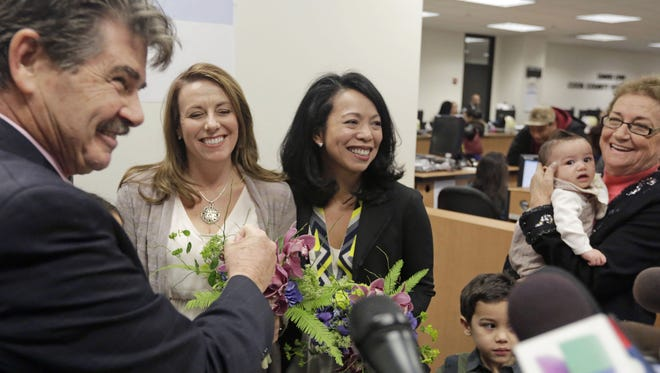 FILE - In this Feb. 21, 2014 file photo, Cook County Clerk David Orr, left, performs a marriage ceremony for Theresa Volpe, second from left, and Mercedes Santos, in Chicago. Same-sex couples in Illinois' Cook County began receiving marriage licenses immediately after a federal judge told clerks to issue licenses even before the law is fully in effect. The move to acknowledge and grant same sex marriage is one of The Associated Press' Top 10 Illinois stories of the year. (AP Photo/M. Spencer Green,File)