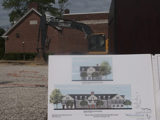 A sign of the new development plans are shown minutes before the demolition of the old bank building at Main Street and Cooper Avenue in Evesham.
