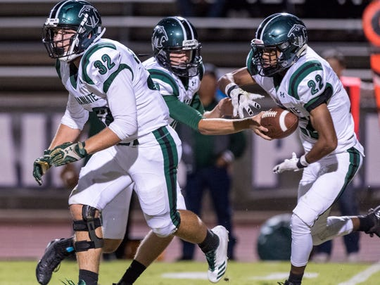El Diamante's Jake Garbani, left, looks down field as Devontae Freeman, right, takes a hand off from quarterback Parker Boswell in a West Yosemite League high school football game against Mt. Whitney on Friday, September 22, 2017.