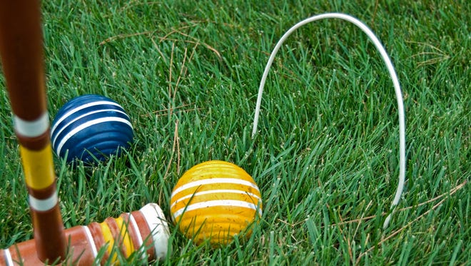 Old croquet mallet and balls in green grass.