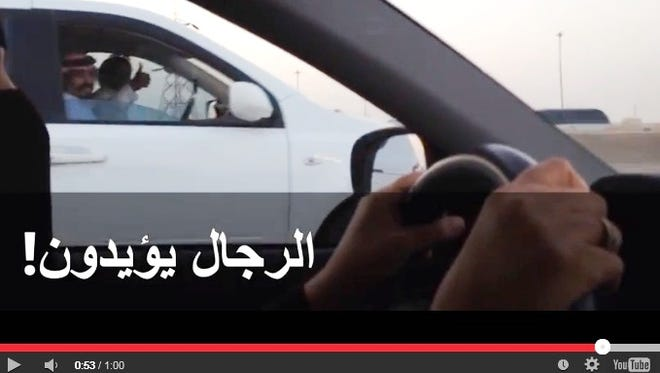 Saudi males in another vehicle give a thumbs up to a woman driving through Riyadh in a YouTube video showing defiance of a ban on women drivers.