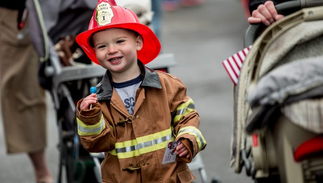 Owen Culloty, 3, of St. Clair, eats a sucker while dressed as a fireman during the annual Safety Town event Saturday, May 14, 2016 in front of Neiman's Family Market in St. Clair.