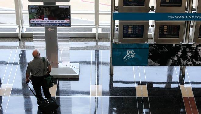A man watches a television report on Hurricane Matthew at Washington's Reagan Natinal Airport on Oct. 7, 2016.