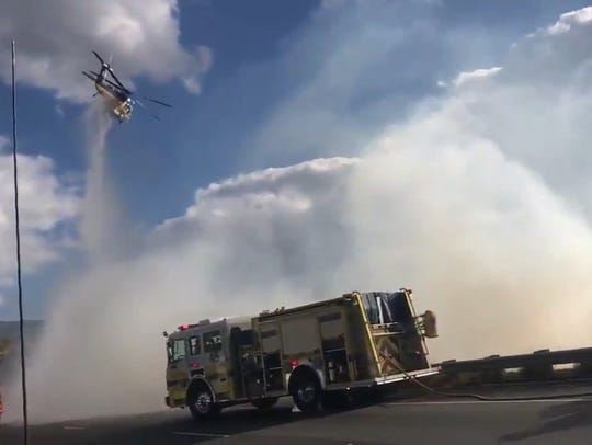A helicopter attacks a spot fire along Highway 118
