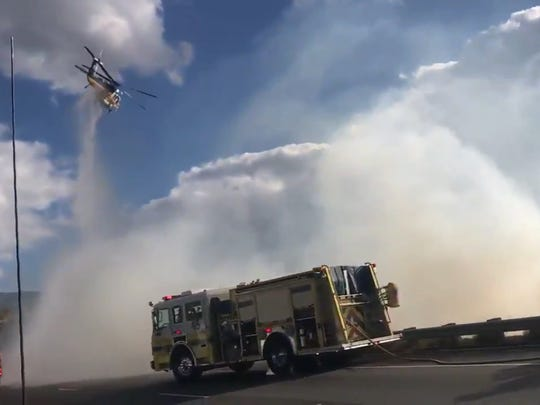 A helicopter attacks a spot fire along Highway 118 in Simi Valley Monday afternoon, as shown in this screenshot from a video tweeted by the California Highway Patrol's Moorpark division.