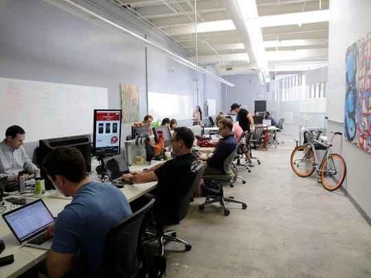 In this Aug. 12, 2014 photo, employees of Rivalry Games work on their computers at technology incubator MuckerLab, in Santa Monica, Calif. The relocation of tech companies to southern California is part of a growing movement of U.S. cities seeking to duplicate the formula that turned northern California's Silicon Valley, slightly south of San Francisco, into a mecca of society-shifting innovation and immense wealth.