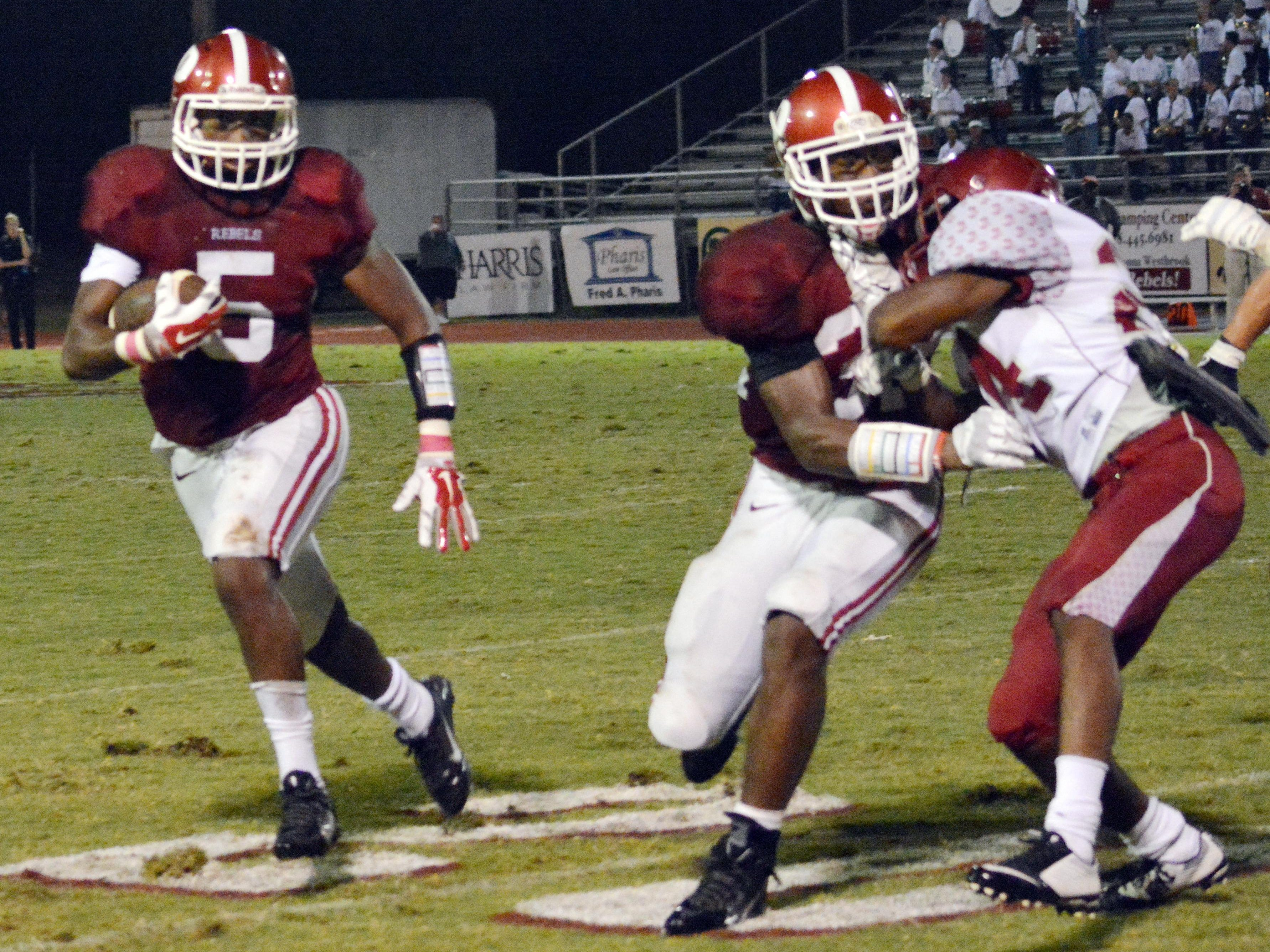 Landon King (32) blocks a Ouachita defender to open space for Jarious Green (5). Green, a senior, and King, a junior, will form a dynamic backfield duo for Pineville in 2015.