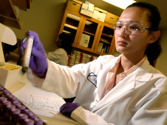 FILE - In this July 22, 2004, file photo, Lily Zimmerman processes blood from a DNA collection kit at California's DNA laboratory in Richmond, Calif.  More police departments are amassing their own DNA databases, a move critics say is a way around stringent regulations governing state crime labs and the national DNA database.