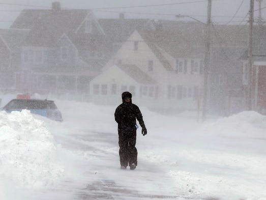 A passerby walks through snow and strong wind along an empty street in Marshfield, Mass. Temperatures across the state were in the single digits.