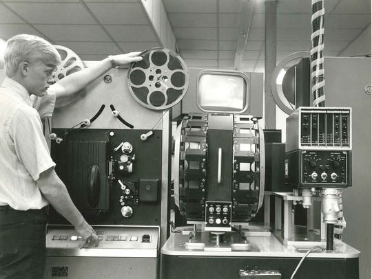 Jimmy Kuddes operates a film projector used to load