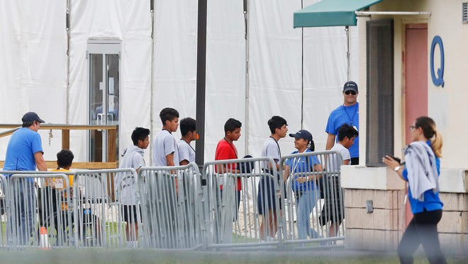 Immigrant children walk in a line outside the Homestead Temporary Shelter for unaccompanied minors, a former Job Corps site that now houses them, on June 20, 2018, in Homestead, Florida.