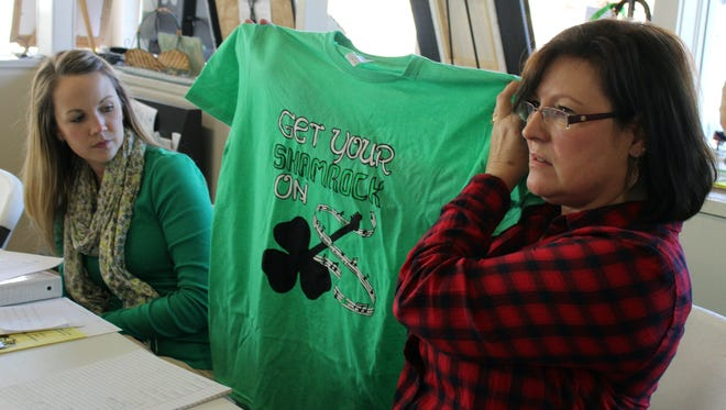 Teresa Mitchell, right, holds up this year's Houston County Area Chamber of Commerce official Irish Day T-shirt. Chamber President Abby Rouse, left, looks at the shirt.