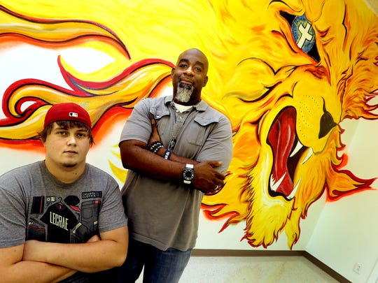 Intern for the Vision Baptist Inner City Community Center, The Den, Davis Wallace, left, and the New Vision Baptist Inner City pastor, Michael L. Davis, stand in front of a 15-foot floor-to-ceiling graffiti-style mural on the back wall of the main room of the center.