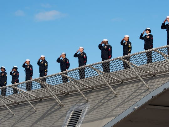 Crew members of the USS Jackson salute from the deck